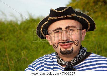 portrait of smiling man with drawed beard and whiskers in pirate suit in early fall evening park