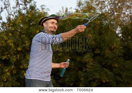 joyful man with drawed beard and whiskers in pirate suit is blowing soap bubbles.