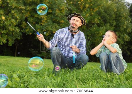 man with drawed beard and whiskers is looking at onesoap bubble