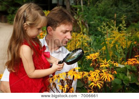 Little girl in red dress with father considers plants through magnifying glass.