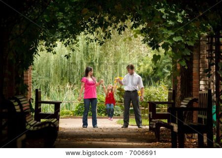 Little girl in red dress with father and mother in park in plant tunnel.