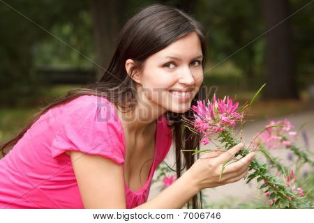 Portrait of smiling girl in summer garden. Girl near to flower looks in camera