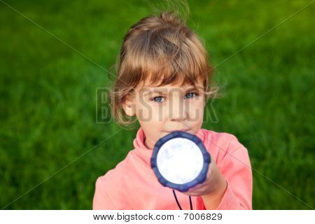 girl playing with lantern. Portrait of girl against a grass. grass background