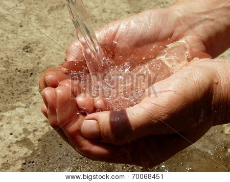 hands catching the stream of water