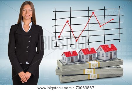 Businesswoman with houses and money