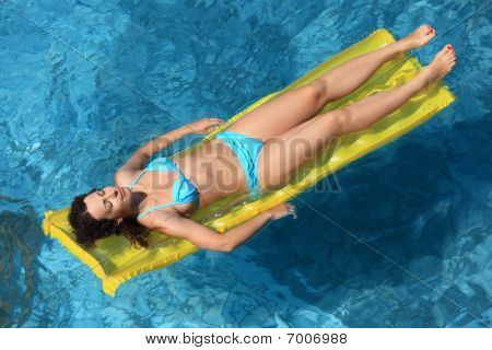 Beautiful Sexual Woman Relaxing On An Inflatable Mattress In Pool