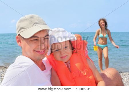 Young Man With Little Girl In Orange Lifejacket And Beautiful Woman With Plastic Toy Bucket On Beach
