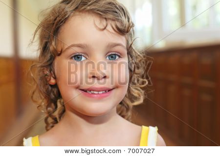 Pretty Smiling Little Girl With Curly Hair In Corridor