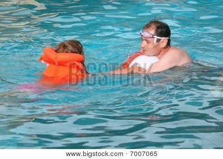Joven y niña en chaleco bañarse en la piscina en Resort