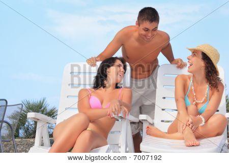 Sonriente hombre y dos jóvenes mujeres reclinables en Chaise salones junto a la piscina aire libre, hablar con ellos