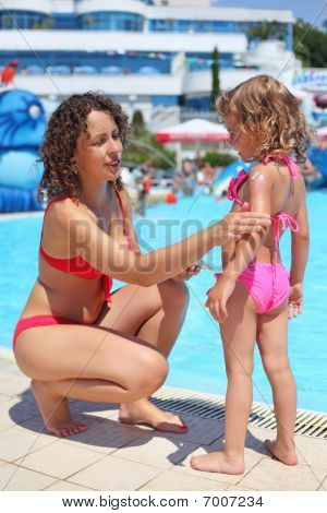 Smiling Beautiful Woman Smears With Cream For Sunburn Little Girl Near Pool In Aquapark