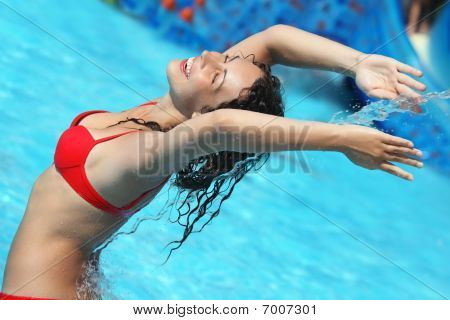 Smiling Beautiful Woman Bathes In Pool Under Water Stream, Lifted Hands Upwards