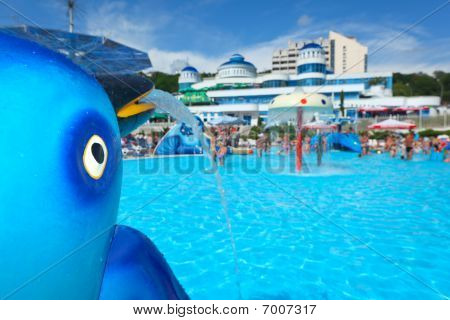Fountain In Form Of Toy Dolphin Near Pool In Aquapark