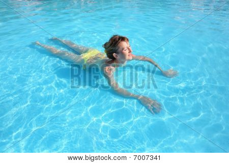 Young Beautiful Woman Swimming In Yellow Bikini In Paddling Pool
