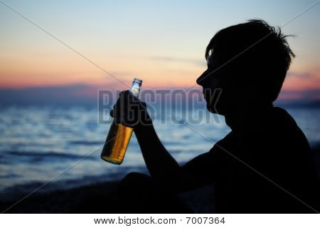 Silhouette Teenager Boy With Beer Bottler On Stone Seacoast In Evening