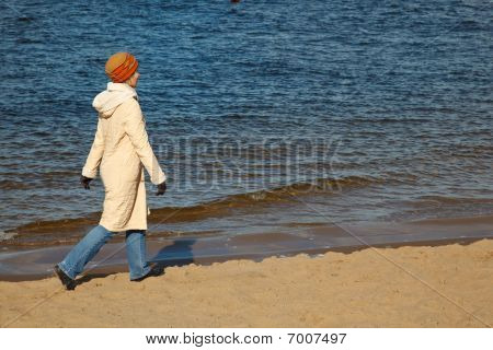 Girl walks on autumn beach in the hat coat jeans and sports shoes.