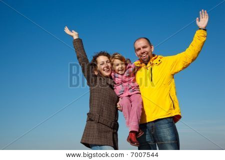 Happy parents together with a daughter with the hands lifted upwards a bright sunny day against the