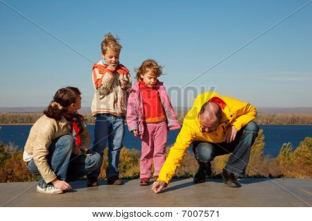 Family from four persons walks in solar autumn day. Parents draw chalk on asphalt.