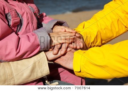 The connected hands of family as support and unity sign. Three people on nature.