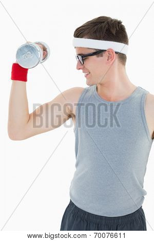 Nerdy hipster lifting heavy dumbbell on white background