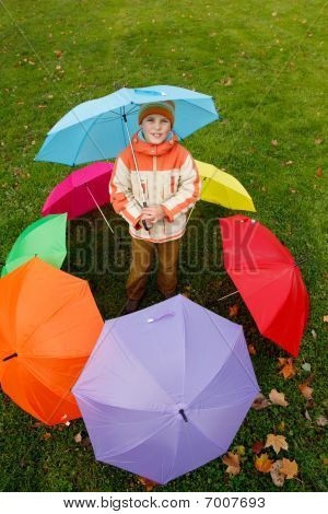Boy in autumn park in environment of multi-coloured umbrellas. Top view.
