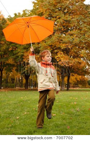 Portrait of smiling boy in autumn park. In hand umbrella looks aside.