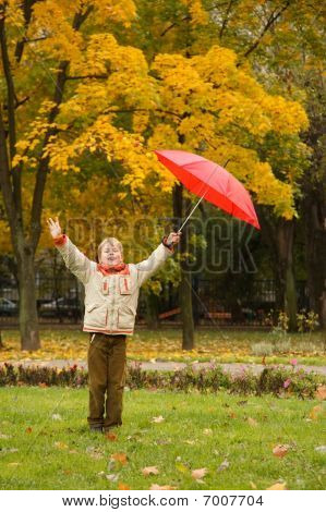 Portrait of boy in autumn park. Hands are lifted in one red umbrella.