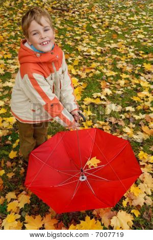 Portrait of boy in autumn park. Holds in lowered hand red umbrella. Top view.