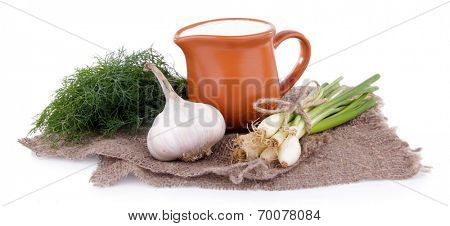 Clay pot with cream and a tuft of onion, dill and garlic near it on a piece of sacking on white background isolated