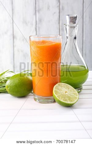 Glass of fresh carrot juice, decanter of lime juice, lime, tuft of grass on the table in front of wooden wall