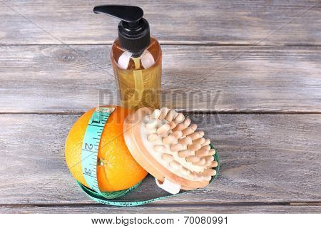 Fresh orange, tapeline, shower gel and a brush on grey wooden table