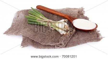 Wooden spoon of cream and a tuft of onion on piece of sacking on white background isolated