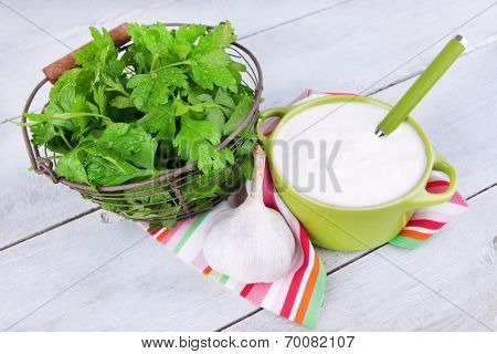 Green pan of cream and a tuft of dill and garlic on a napkin on wooden background
