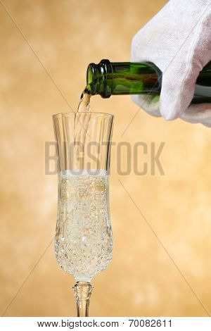 A waiter pours, crisp, delicious champagne into a stylish glass, poised against a golden, mottled background.