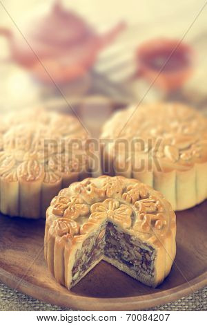 Retro vintage style Chinese mid autumn festival foods. The Chinese words on the mooncakes means assorted fruits nuts, not a logo or trademark. Traditional mooncakes on table setting with teacup.