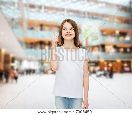 advertising, childhood, gesture, consumerism and people - smiling girl in white t-shirt pointing finger up over shopping center background