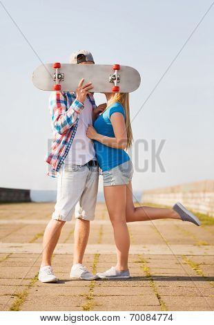 holidays, vacation, love and people concept - couple kissing and hiding their faces behind skateboard outdoors