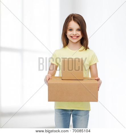 advertising, childhood, delivery, mail and people - smiling little girl holding cardboard boxes over white room background