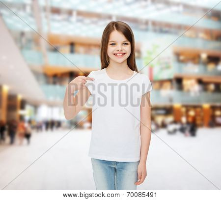 advertising, childhood, gesture and people - smiling girl in white t-shirt pointing finger on herself over shopping center background