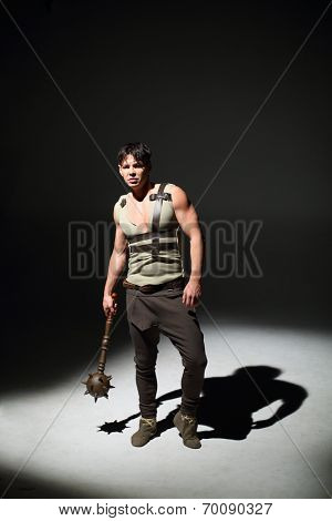 Handsome young man standing with a mace in hand in a dark studio