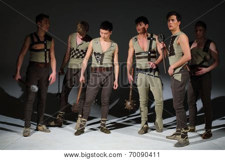 A group of six young people with maces looking in different directions