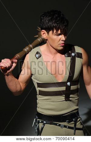 Strong young man in a costume put mace on his shoulder in a dark studio