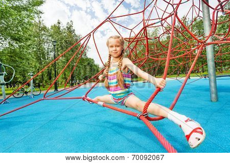 Active girl sits on red ropes in leg-split