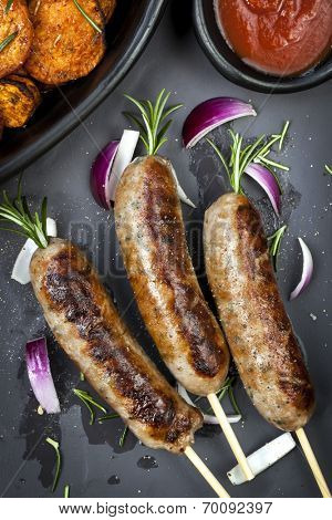 Grilled sausages with rosemary, sweet potato fries, and red onion.