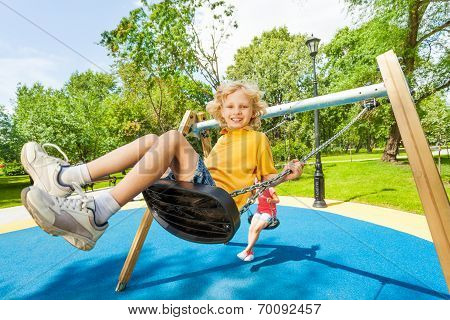 Boy swings in opposite direction to the girl
