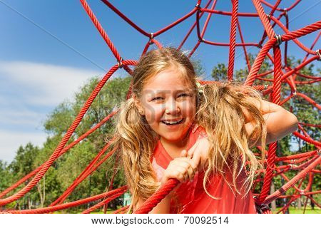 Pretty girl holding rope of red web in summer