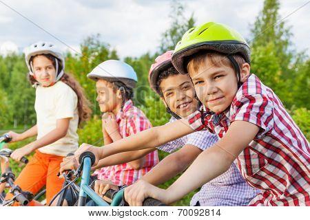 Looking boy in helmet with his friends behind