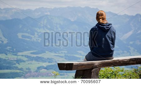 Woman On Alpine Trail Bench