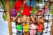 foto of mating  - Many kids look though gridlines of playground and smile happily - JPG