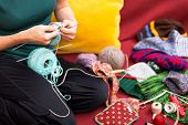 picture of knitting  - closeup of a knitting woman sitting on a couch - JPG